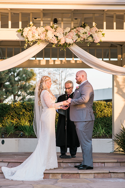 Orange county outdoor wedding shoot at turnip rose garden bride form fitting gown with lace detail and long sleeves with long veil and sweetheart neckline with groom heather grey notch lapel suit with matching vest and white dress shirt with long white tie and blush pink floral boutonniere standing holding hands during ceremony