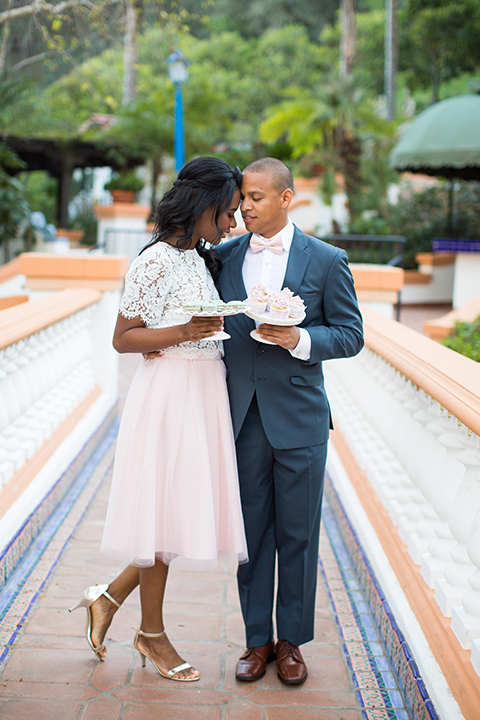 Rancho las lomas outdoor engagement shoot bride light pink tulle skirt with a white lace short sleeve top with groom slate blue notch lapel suit with a white dress shirt and blush pink bow tie with a pink floral boutonniere standing and hugging holding desserts