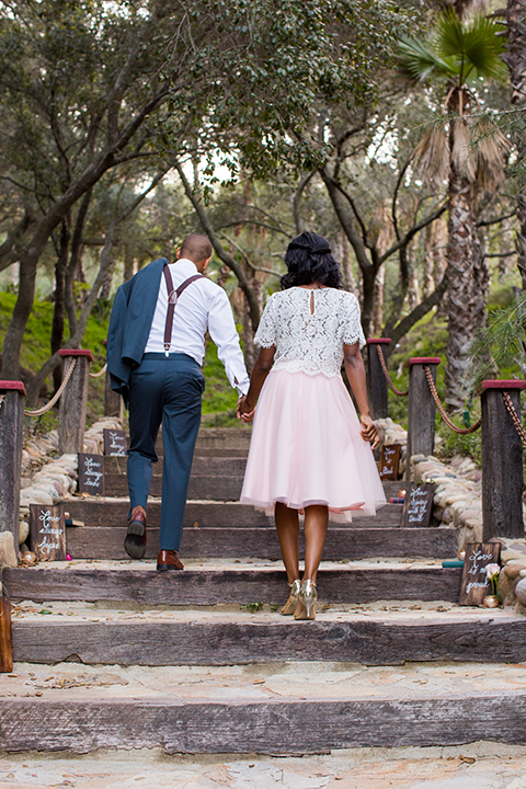 Rancho las lomas outdoor engagement shoot bride light pink tulle skirt with a white lace short sleeve top with groom slate blue notch lapel suit with a white dress shirt and blush pink bow tie with a pink floral boutonniere holding hands and walking up stairs after wedding ceremony