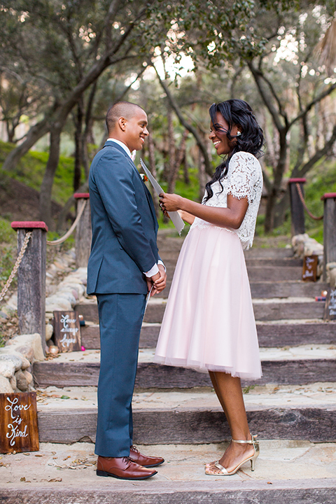 Rancho las lomas outdoor engagement shoot bride light pink tulle skirt with a white lace short sleeve top with groom slate blue notch lapel suit with a white dress shirt and blush pink bow tie with a pink floral boutonniere standing on stairs during ceremony reading vows