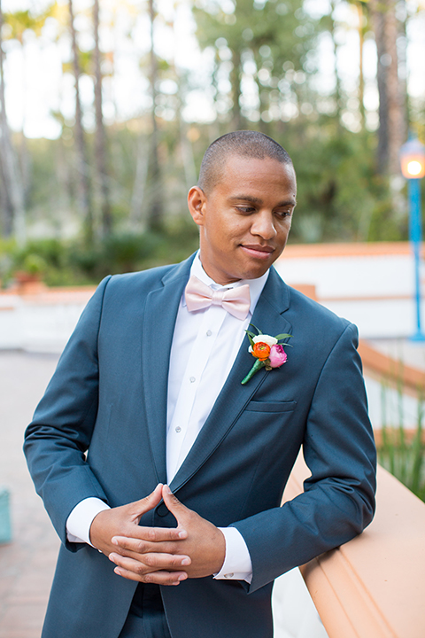 Rancho las lomas outdoor engagement shoot groom slate blue notch lapel suit with a white dress shirt and blush pink bow tie with a pink floral boutonniere