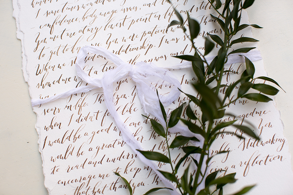 Rancho las lomas outdoor engagement shoot wedding vows on white paper in small cursive writing and white ribbon tied in a bow for decor and greenery florals wedding photo idea for vows