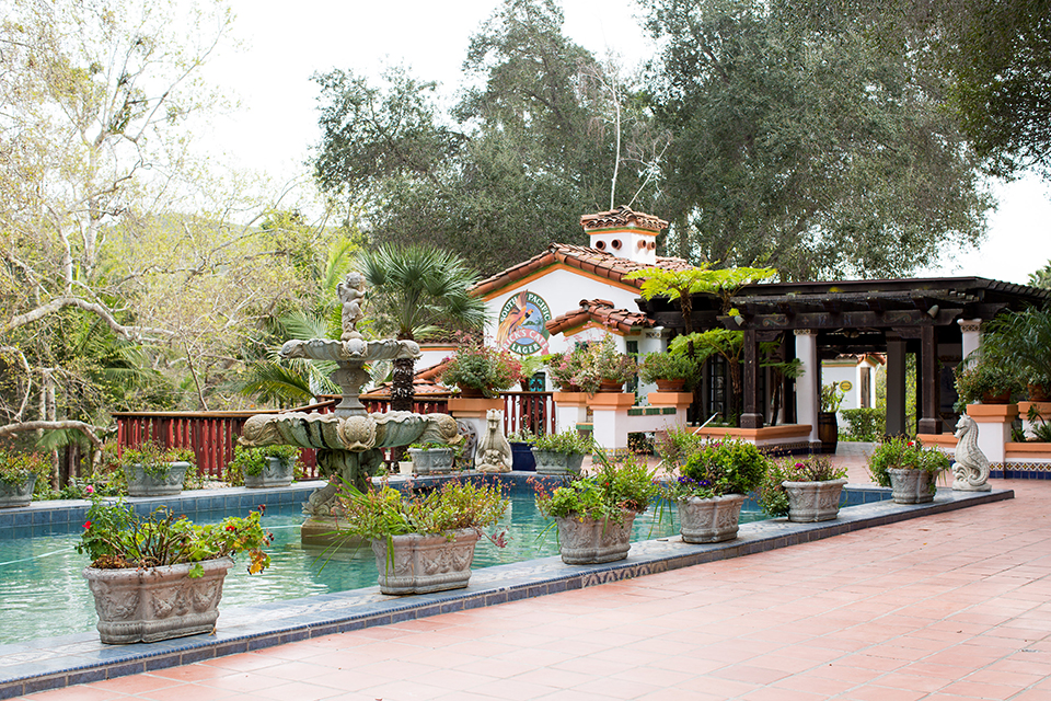Rancho las lomas outdoor engagement shoot wedding venue outdoor building with water and green plants with brick walkway and arches wedding photo idea for venue