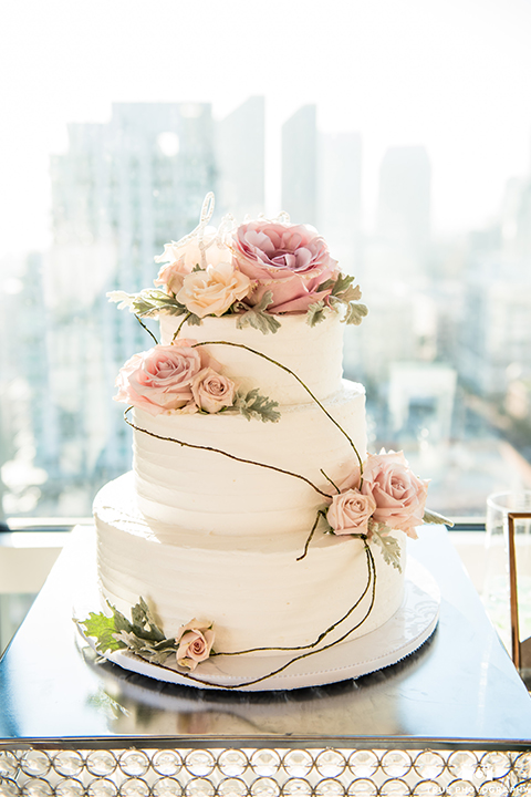 San diego outdoor wedding at the ultimate skybox reception table set up white table linen with gold and white chairs and pink napkin decor with white and blush pink flower centerpiece decor and table numbers with wedding cake three tier white cake with blush pink flower decor on top and on sides