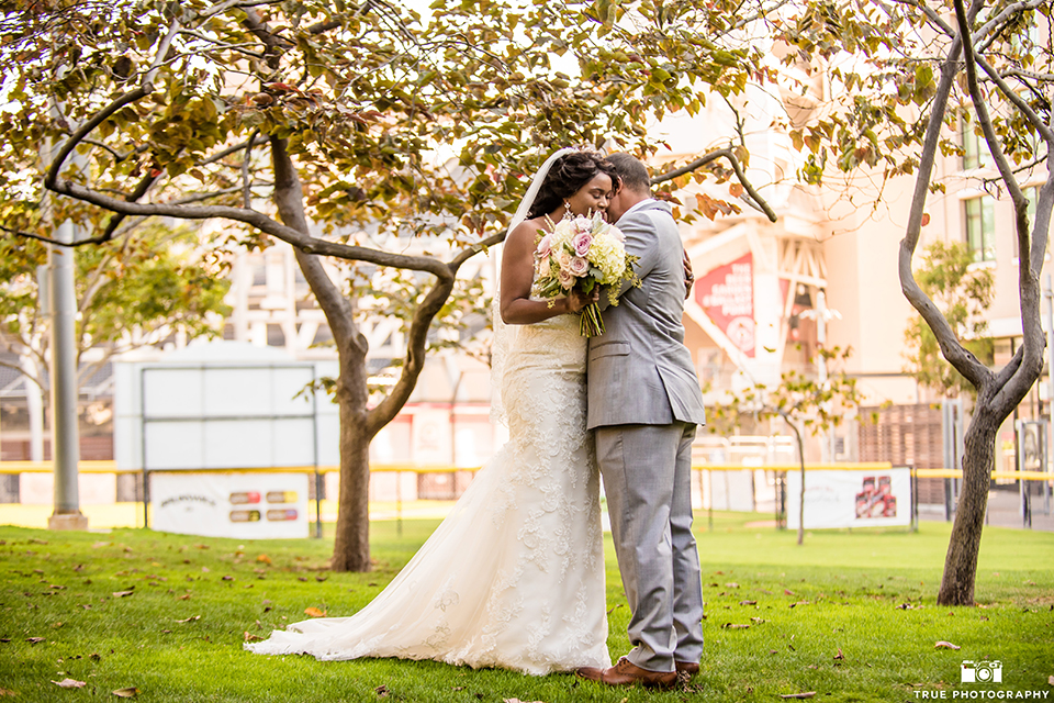 San diego outdoor wedding at ultimate skybox bride form fitting strapless lace gown with a sweetheart neckline and crystal belt with long veil and groom heather grey notch lapel suit with a white dress shirt and matching vest with a long white tie and white floral boutonniere first look bride and groom hugging and bride holding white floral bridal bouquet