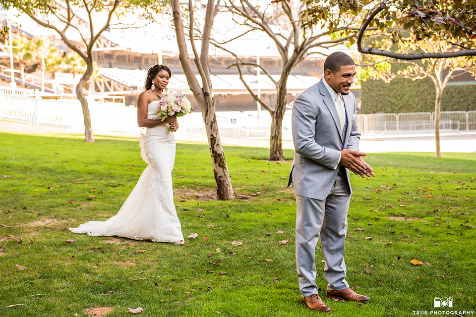 San diego outdoor wedding at ultimate skybox bride form fitting strapless lace gown with a sweetheart neckline and crystal belt with long veil and groom heather grey notch lapel suit with a white dress shirt and matching vest with a long white tie and white floral boutonniere first look bride walking behind groom holding white floral bridal bouquet