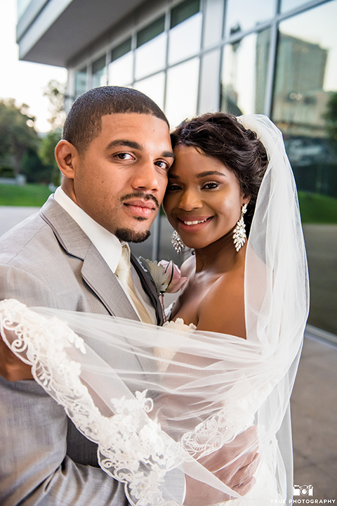 San diego outdoor wedding at ultimate skybox bride form fitting strapless lace gown with a sweetheart neckline and crystal belt with long veil and groom heather grey notch lapel suit with a white dress shirt and matching vest with a long white tie and white floral boutonniere hugging