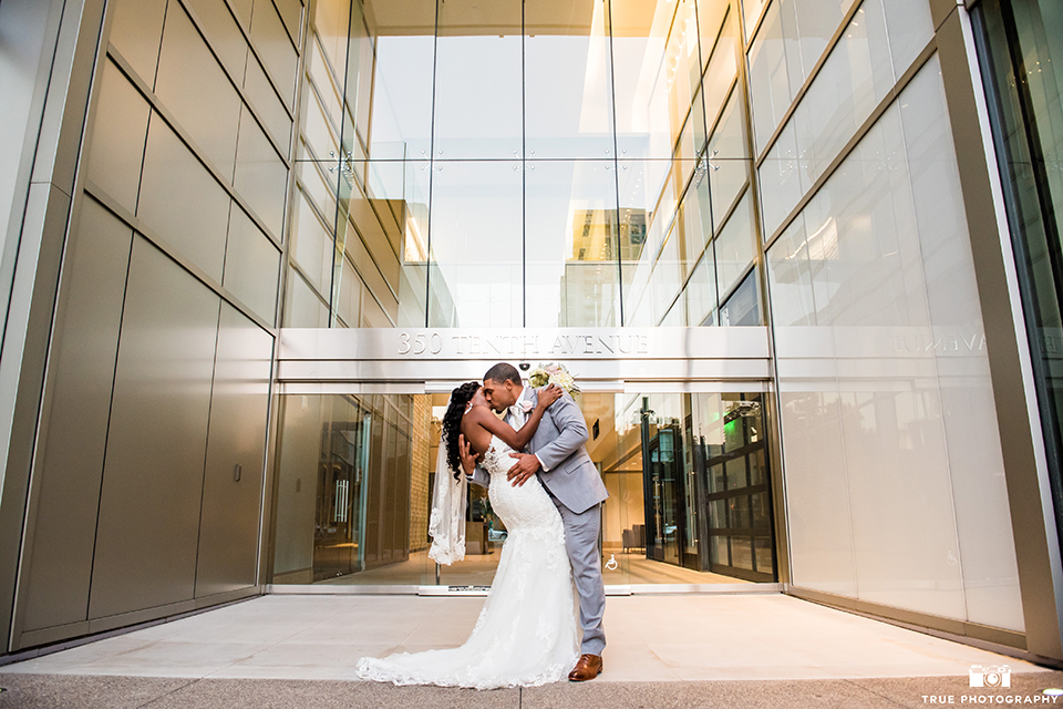 San diego outdoor wedding at ultimate skybox bride form fitting strapless lace gown with a sweetheart neckline and crystal belt with long veil and groom heather grey notch lapel suit with a white dress shirt and matching vest with a long white tie and white floral boutonniere kissing