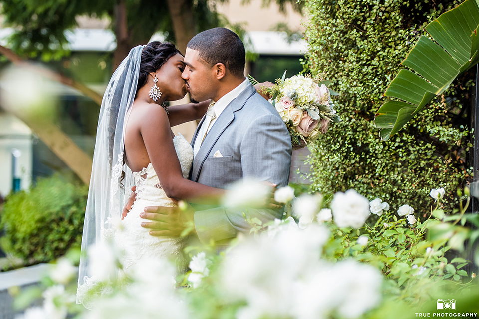San diego outdoor wedding at ultimate skybox bride form fitting strapless lace gown with a sweetheart neckline and crystal belt with long veil and groom heather grey notch lapel suit with a white dress shirt and matching vest with a long white tie and white floral boutonniere kissing and bride holding white floral bridal bouquet