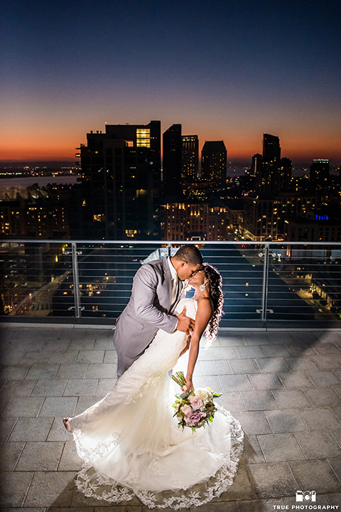 San diego outdoor wedding at ultimate skybox bride form fitting strapless lace gown with a sweetheart neckline and crystal belt with long veil and groom heather grey notch lapel suit with a white dress shirt and matching vest with a long white tie and white floral boutonniere standing and kissing at night bride holding white floral bridal bouquet