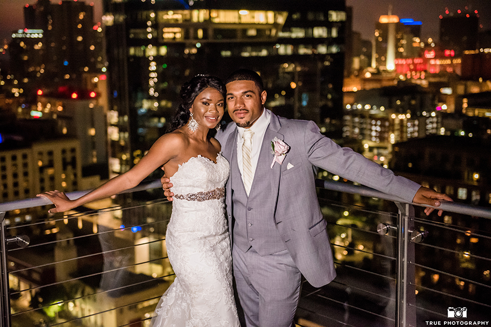 San diego outdoor wedding at ultimate skybox bride form fitting strapless lace gown with a sweetheart neckline and crystal belt with long veil and groom heather grey notch lapel suit with a white dress shirt and matching vest with a long white tie and white floral boutonniere standing and hugging at night