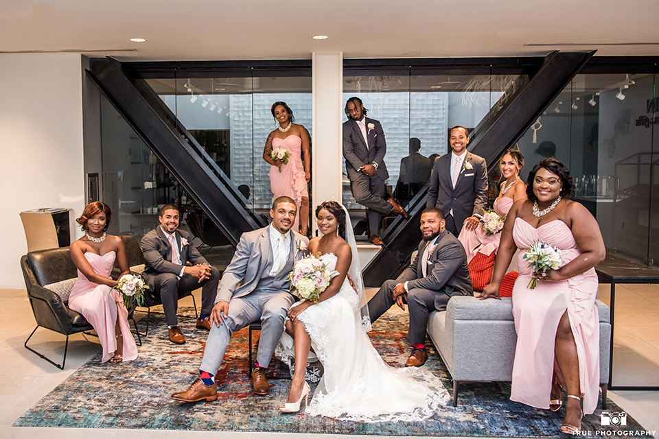 San diego outdoor wedding at ultimate skybox bride form fitting strapless lace gown with a sweetheart neckline and crystal belt with long veil and groom heather grey notch lapel suit with a white dress shirt and matching vest with a long white tie and white floral boutonniere sitting with wedding party bridesmaids long blush pink dresses and groomsmen charcoal grey suits with long white ties