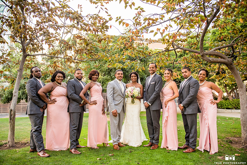 San diego outdoor wedding at ultimate skybox bride form fitting strapless lace gown with a sweetheart neckline and crystal belt with long veil and groom heather grey notch lapel suit with a white dress shirt and matching vest with a long white tie and white floral boutonniere with wedding party standing bridesmaids long blush pink dresses and groomsmen charcoal grey suits with long white ties