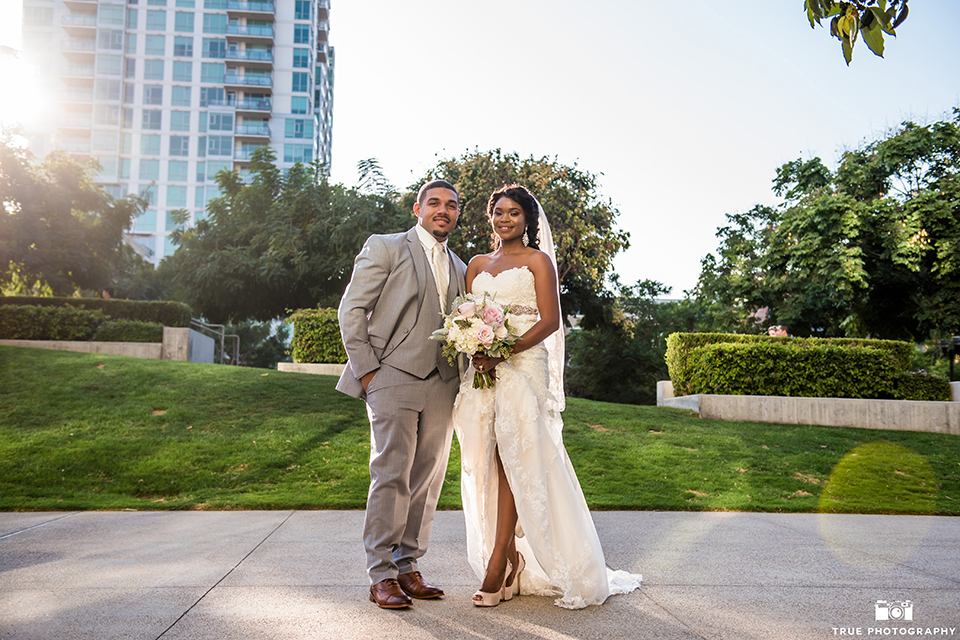 San diego outdoor wedding at ultimate skybox bride form fitting strapless lace gown with a sweetheart neckline and crystal belt with long veil and groom heather grey notch lapel suit with a white dress shirt and matching vest with a long white tie and white floral boutonniere standing and hugging bride holding white floral bridal bouquet