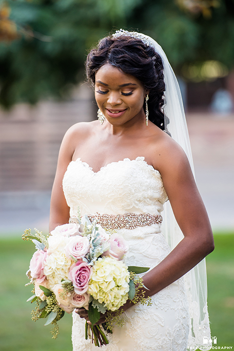 San diego outdoor wedding at ultimate skybox bride form fitting strapless lace gown with a sweetheart neckline and crystal belt with long veil holding white floral bridal bouquet