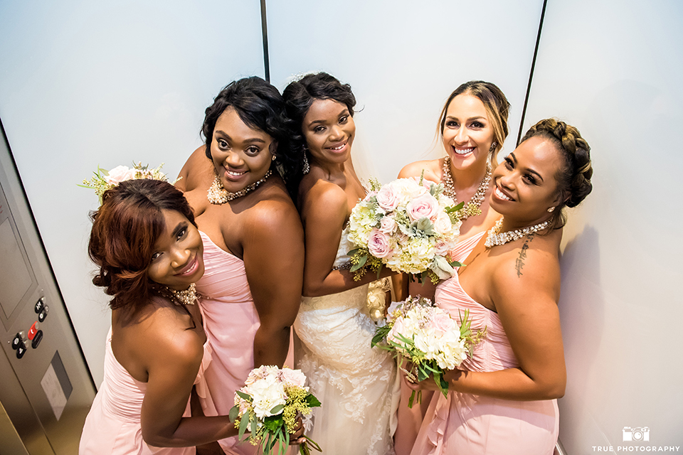 San diego outdoor wedding at ultimate skybox bride form fitting strapless lace gown with a sweetheart neckline and crystal belt with long veil holding white floral bridal bouquet with bridesmaids long blush pink dresses holding white floral bridal bouquets