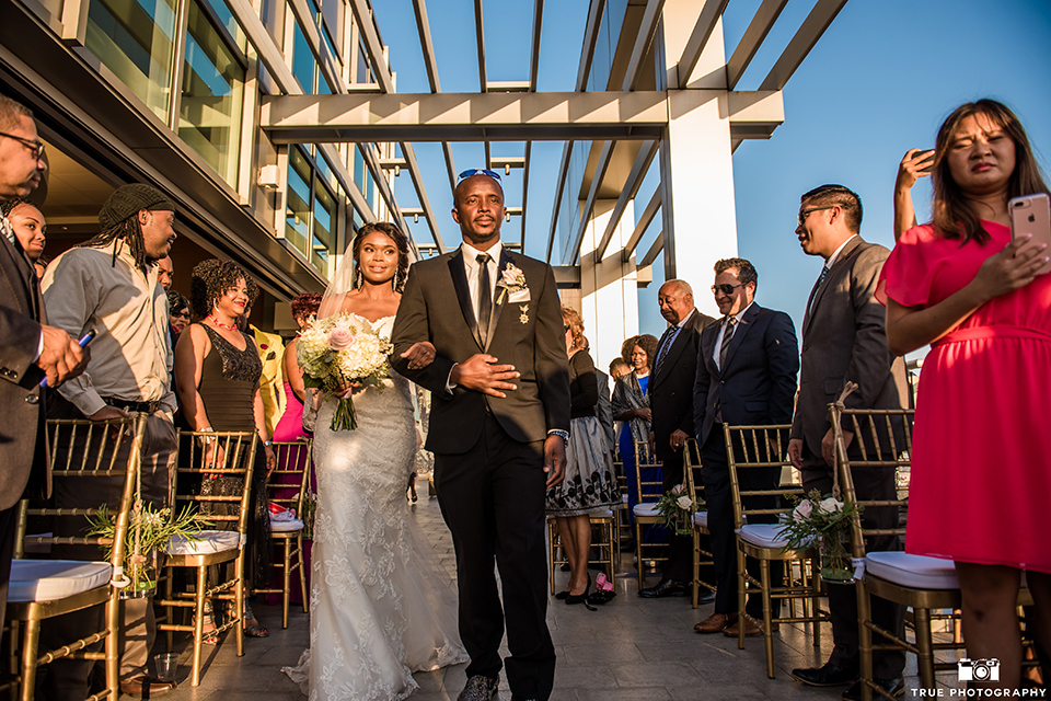 San diego outdoor wedding at ultimate skybox bride form fitting strapless lace gown with a sweetheart neckline and crystal belt with long veil holding white floral bridal bouquet walking down the aisle with dad holding white floral bridal bouquet