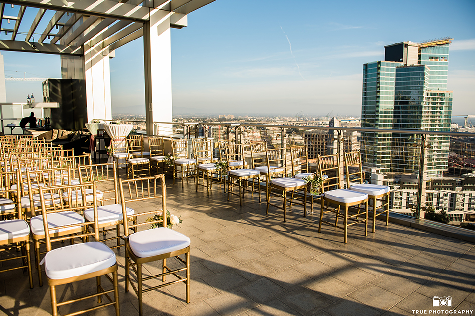 San diego outdoor wedding at ultimate skybox ceremony set up with white and gold chiavari chairs and city views with rooftop ceremony and buildings in background wedding photo idea for ceremony set up