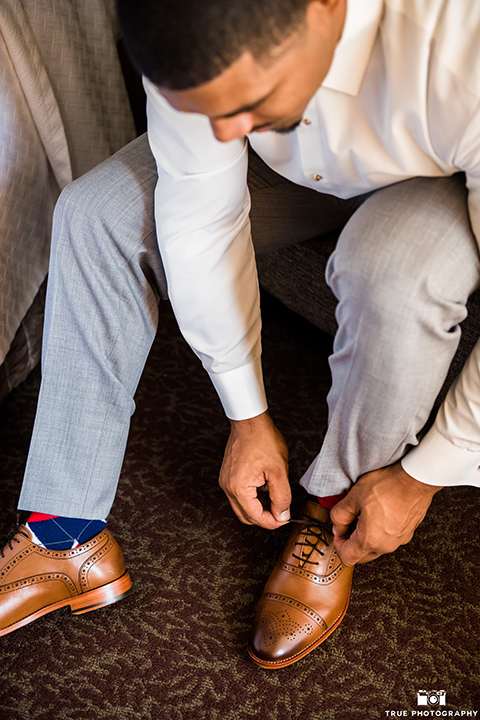San diego outdoor wedding at ultimate skybox groom heather grey notch lapel suit with a white dress shirt and matching vest with a long white tie and white pocket square with a white floral boutonniere getting ready and putting on shoes