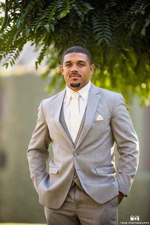 San diego outdoor wedding at ultimate skybox groom heather grey notch lapel suit with a white dress shirt and matching vest with a long white tie and white pocket square with a white floral boutonniere