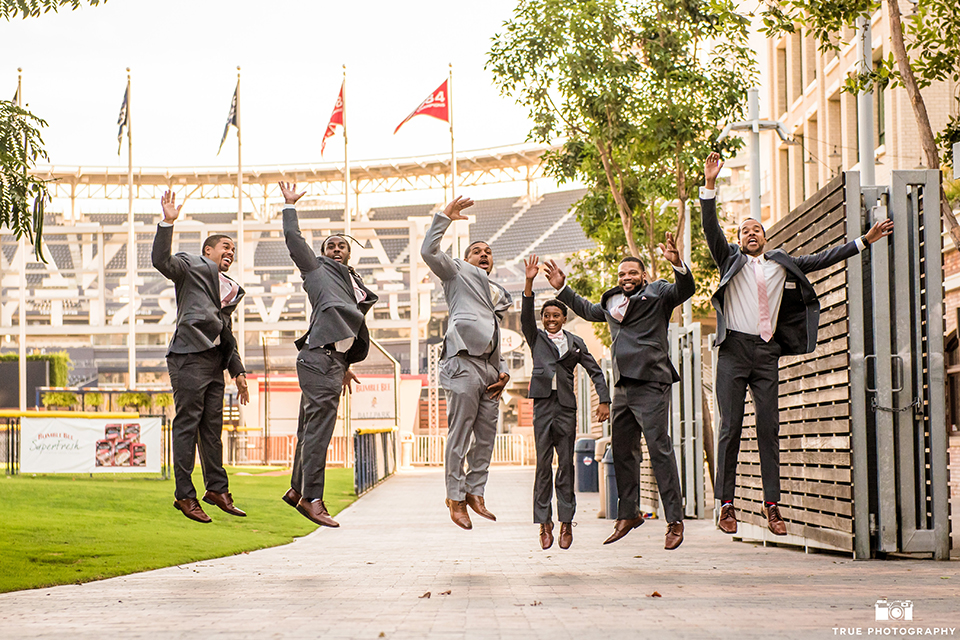 San diego outdoor wedding at ultimate skybox groom heather grey notch lapel suit with a white dress shirt and matching vest with a long white tie and white pocket square with a white floral boutonniere with groomsmen charcoal grey suits with long white ties jumping