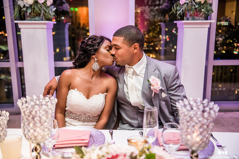 San diego outdoor wedding at ultimate skybox bride form fitting strapless lace gown with a sweetheart neckline and crystal belt with long veil and groom heather grey notch lapel suit with a white dress shirt and matching vest with a long white tie and white floral boutonniere reception sitting at sweetheart table kissing