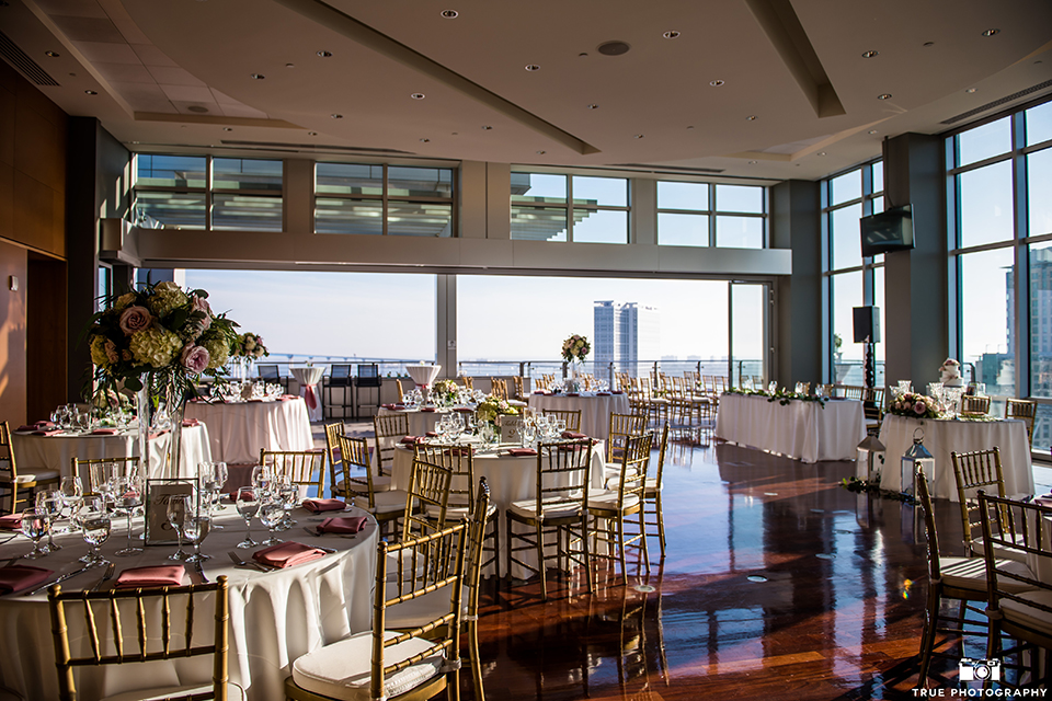 San diego outdoor wedding at the ultimate skybox reception table set up white table linen with gold and white chairs and pink napkin decor with white and blush pink flower centerpiece decor and table numbers
