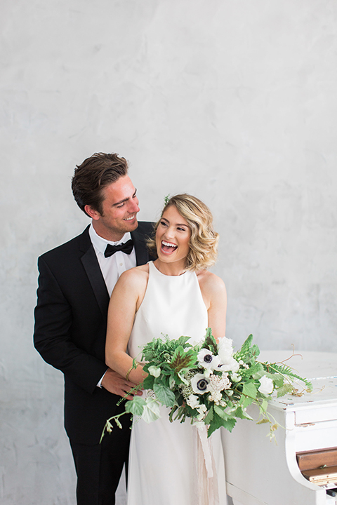 Downtown los angeles wedding shoot at fd photo studio bride form fitting simple gown with a high halter neckline and groom black notch lapel tuxedo by michael kors with a white dress shirt and black bow tie hugging and laughing bride holding white and green floral bridal bouquet