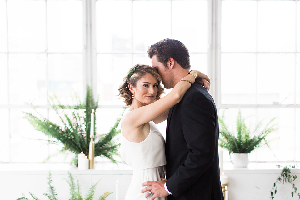 Downtown los angeles wedding shoot at fd photo studio bride form fitting simple gown with a high halter neckline and groom black notch lapel tuxedo by michael kors with a white dress shirt and black bow tie hugging and smiling with greenery decor