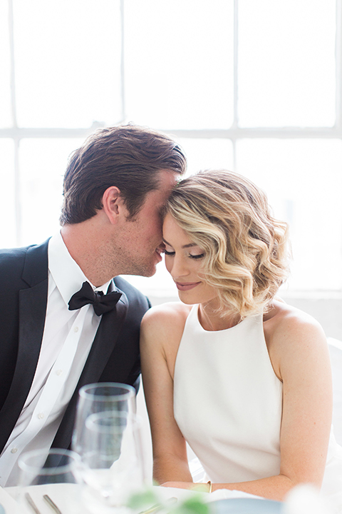 Downtown los angeles wedding shoot at fd photo studio bride form fitting simple gown with a high halter neckline and groom black notch lapel tuxedo by michael kors with a white dress shirt and black bow tie sitting at table hugging and smiling