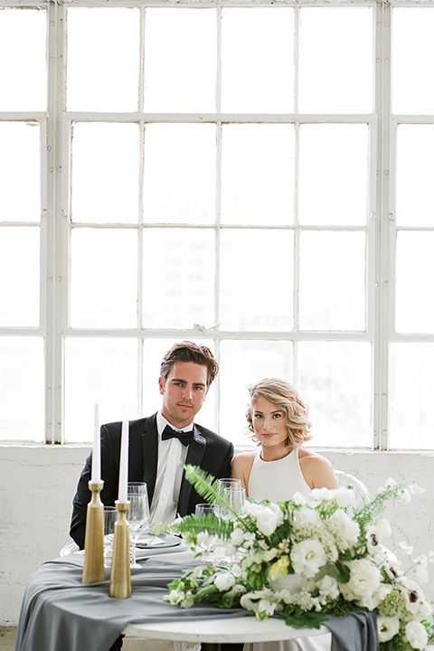 Downtown los angeles wedding shoot at fd photo studio bride form fitting simple gown with a high halter neckline and groom black notch lapel tuxedo by michael kors with a white dress shirt and black bow tie sitting at table