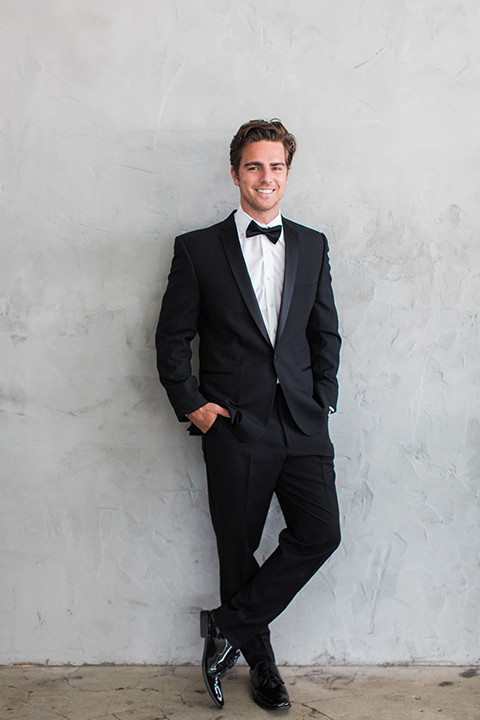 Downtown los angeles wedding shoot at fd photo studio groom black notch lapel tuxedo by michael kors with a white dress shirt and black bow tie standing against wall with hands in pockets
