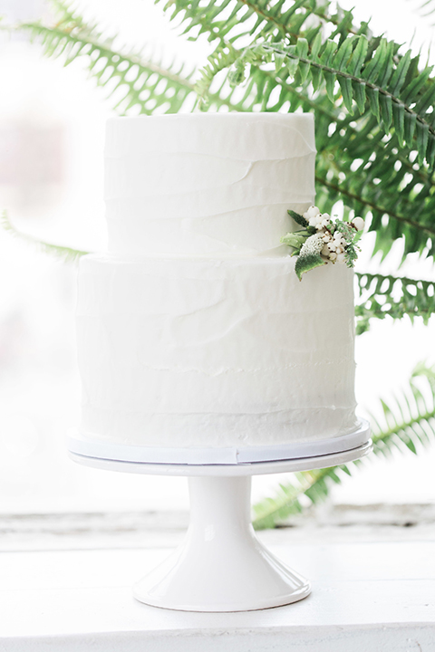 Downtown los angeles wedding shoot at fd photo studio table set up with grey table linen and white and green flower decor with clear ghost chairs and white and grey place settings with white candle decor and piano with two tier white wedding cake with white and green flower decor