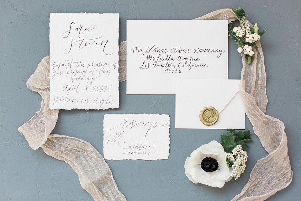 Downtown los angeles wedding shoot at fd photo studio white wedding invitations with black calligraphy writing and white flowers with ribbon decor on grey background wedding photo idea for invitations
