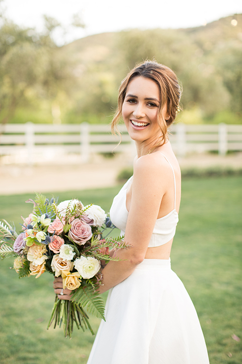 Los angeles outdoor wedding at brookview ranch bride two piece wedding dress with tulle skirt and crop top bodice with thin straps and a sweetheart neckline holding white and pink floral bridal bouquet close up