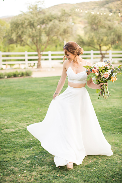 Los angeles outdoor wedding at brookview ranch bride two piece wedding dress with tulle skirt and crop top bodice with thin straps and a sweetheart neckline holding white and pink floral bridal bouquet