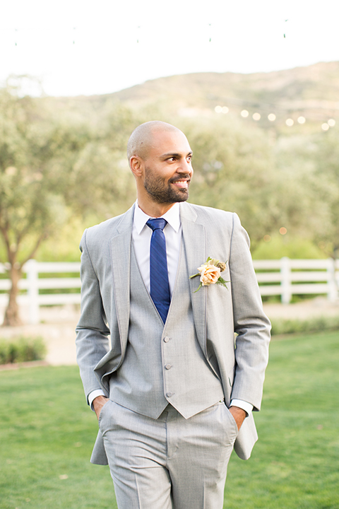 Los angeles outdoor wedding at brookview ranch groom heather grey notch lapel suit with a matching vest and white dress shirt and long blue tie and white floral boutonniere standing with hands in pockets