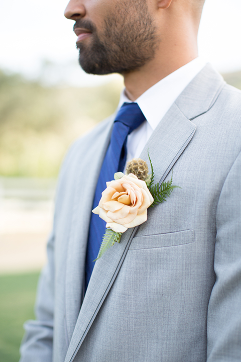 Los angeles outdoor wedding at brookview ranch groom heather grey notch lapel suit with a matching vest and white dress shirt and long blue tie and white floral boutonniere standing close up