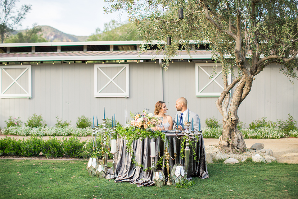 Los angeles outdoor wedding at brookview ranch bride two piece wedding dress with tulle skirt and crop top bodice with thin straps and a sweetheart neckline and groom heather grey notch lapel suit with a matching vest and white dress shirt with a long navy blue tie and white floral boutonniere sitting at table
