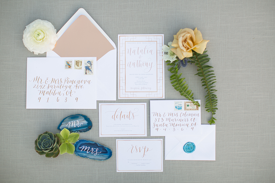 Los angeles outdoor wedding at brookview ranch wedding invitations white invitations with blush pink border and blue seal with white envelopes and blue marble rock decor with white calligraphy writing and grey background wedding photo idea for invitations