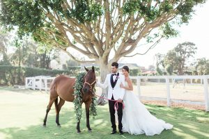 Santa barbara outdoor wedding at the cottages at polo run bride strapless ball gown with a sweetheart neckline and a ruffled skirt with lace detail on bodice with groom white shawl lapel tuxedo with black pants and a black vest with a black bow tie and bright pink floral boutonniere standing with horse