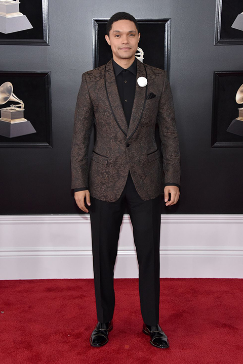 2018 grammys trevor noah brown patterned tuxedo coat with shawl lapel and black  pants with a black dress shirt and long black tie with a white flower lapel pin