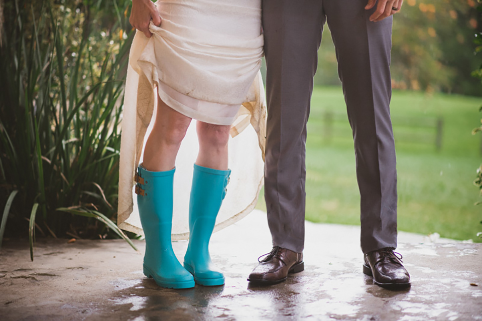 Temecula outdoor wedding at temecula creek inn bride form fitting simple strapless gown with a straight neckline and teal rain boots with groom grey notch lapel suit with a white dress shirt and long brown tie with an orange floral boutonniere shoes with bride wearing teal rain boots