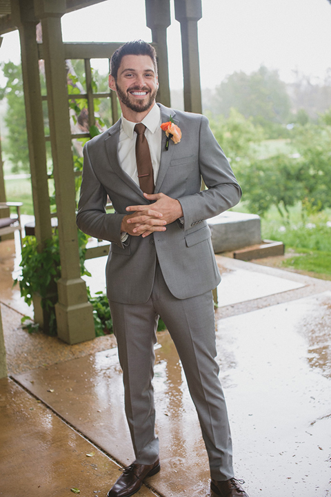 Temecula outdoor rainy wedding at temecula creek inn groom heather grey notch lapel suit with a white dress shirt and a long brown tie with a colorful floral boutonniere standing holding hands