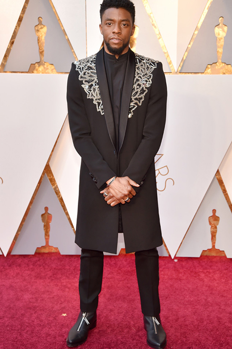 2018 academy awards chadwick boseman black tuxedo with patterned design on jacket with black dress shirt and black pants with black shoes